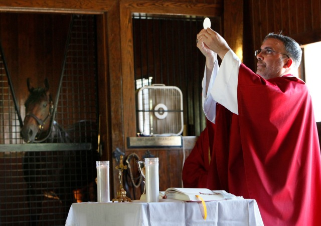 Bishop John Stowe of Lexington, Ky., raises the Eucharist during Mass on Sept. 21 at Ashford Stud Farm. On the left, 2015 Triple Crown Winner American Pharoah watches Mass from his stall. The Mass was part of Chicago Auxiliary Bishop John Manz's pastoral visit to migrant workers in Kentucky on behalf of the USCCB Sept. 19-22, 2016. (CNS photo/Karen Callaway/Catholic New World)