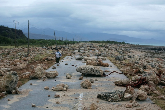 A woman walks on a highway blocked by rocks Oct. 5 after Hurricane Matthew swept through Guantanamo province in Cuba. The powerful hurricane left serious damage at the eastern end of the island, with landslides, toppling electricity poles and cutting off roads by flooding. (CNS photo/Alexandre Meneghini, Reuters)