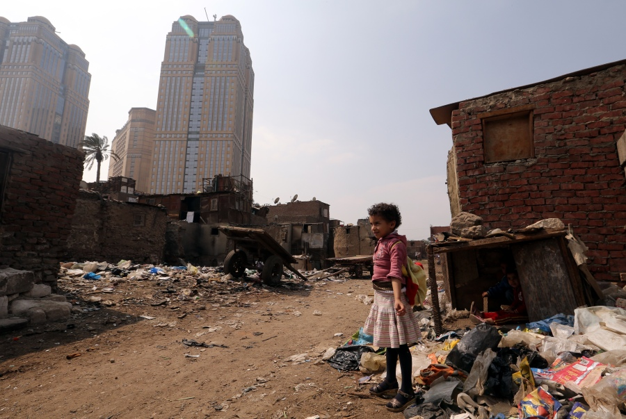 epaselect epa04664840 A child stands in a slum behind Nile City Towers, in Ramlet Bulaq neighborhood, Cairo, Egypt, 16 March 2015. Ramlet Bulaq's residents live in run-down shacks and lack basic facilities, such as running water. They make for an extreme juxtaposition with the gleaming Nile City Towers, home to wealthy companies, a nightclub and the Fairmont Hotel, which has a swimming pool on its roof.  During an investment conference that wrapped up activities on 15 March, the Egyptian government signed a 45 billion dollar agreement with an Emirati company to develop a new administrative capital east of Cairo.  EPA/KHALED ELFIQI