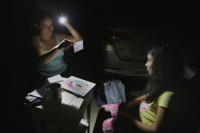 Margarita Rodriguez holds a flashlight as she quizzes her 11-year-old daughter, Isel Martinez, about homework outside their home in San Juan, Puerto Rico, Oct. 25. Most of Puerto Rico was without power and water for more than a month after Hurricane Maria devastated the island. (CNS/Bob Roller)